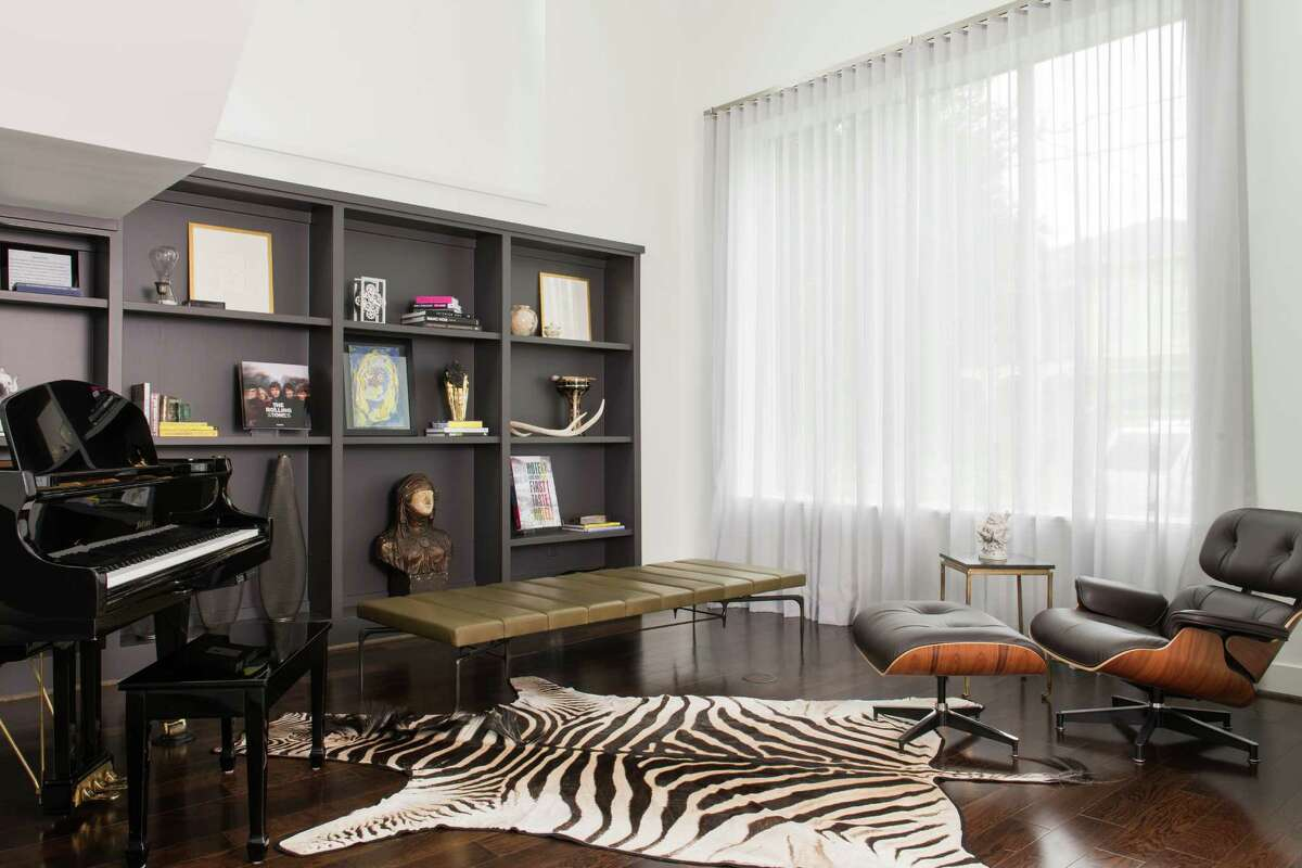 Rick Goldberg is a bachelor, but his Montrose home is an ode to family. The bookcase in this piano room is filled with thoughtful pieces, including artwork from when his daughter was in elementary school. The furniture suits his style: an Eames lounge chair and ottoman, leather daybed, zebra-skin rug and a piano.