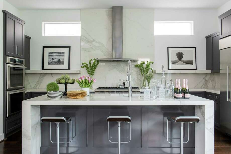 Rick Goldberg had cabinets removed from the back wall to create spaces to display artwork. His Montrose home has a big pantry, so he didn't feel like he was losing storage space. His decorator Selena MacKay also swapped out granite for slabs of Italian porcelain tile, which looks like Calacatta marble but is more stain, chip and scratch resistant. Photo: Michael Hunter