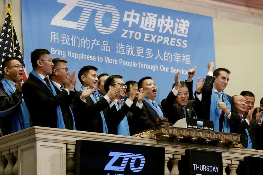 ZTO Express Founder, Chairman and CEO Meisong Lai, center, and members of the company's leadership team celebrate as they ring the New York Stock Exchange opening bell, Thursday, Oct. 27, 2016, to commemorate the company's IPO. (AP Photo/Richard Drew) Photo: Richard Drew, Associated Press