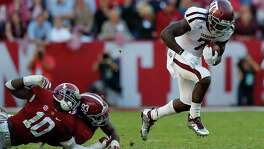 Texas A&M's Keith Ford (7) breaks a tackle by Alabama's Reuben Foster (10) and Jonathan Allen (93) during a run at Bryant-Denny Stadium on Oct. 22, 2016 in Tuscaloosa, Ala.