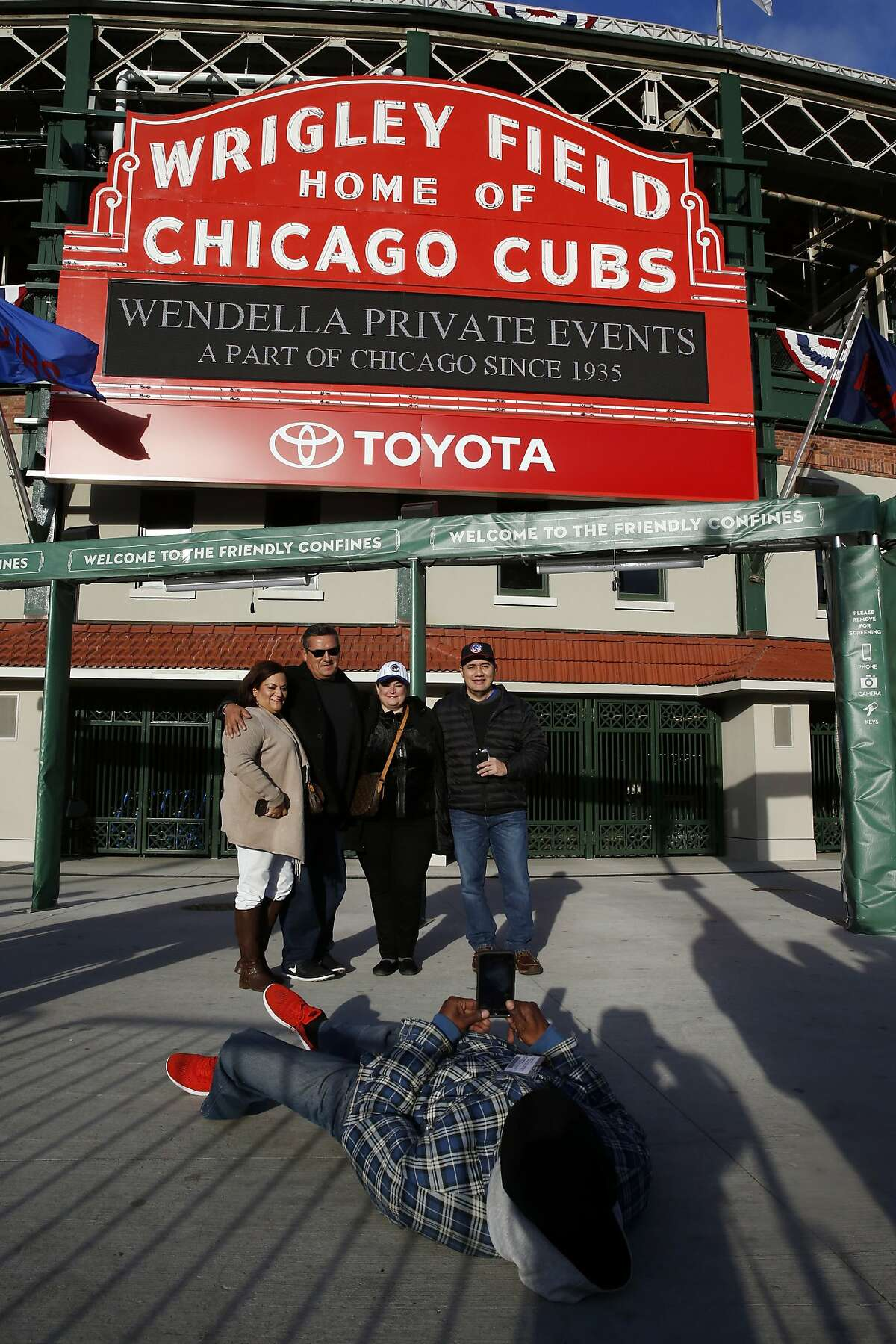 Fans gather in front of the marquee at Wrigley Field for a picture before Friday's Game 3 of the Major League Baseball World Series between the Chicago Cubs and the Cleveland Indians, Thursday, Oct. 27, 2016, in Chicago. (AP Photo/Nam Y. Huh)