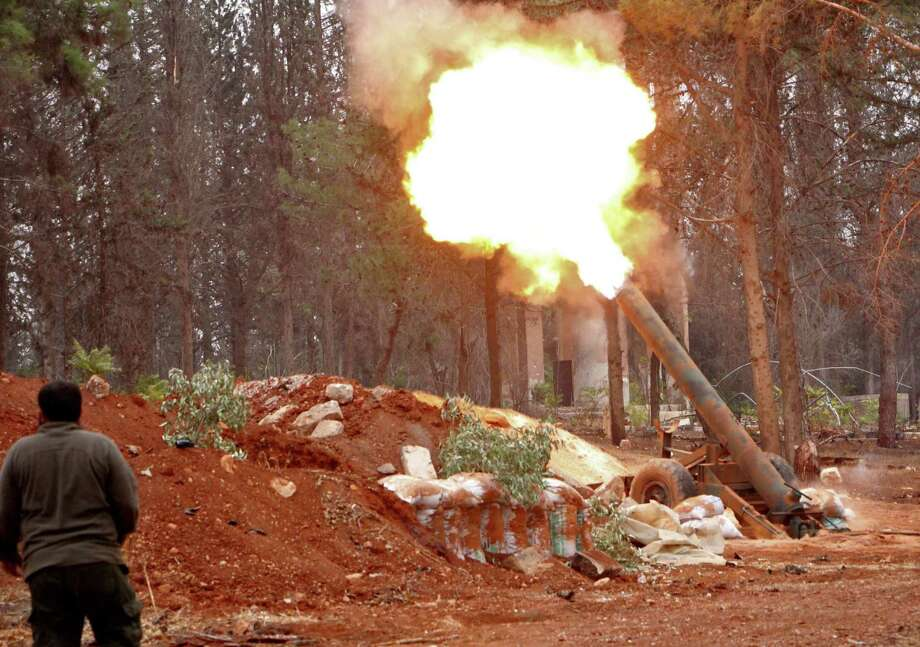 Rebel fighters from the Jaish al-Fatah brigades fire a home-made mortar launcher during a major assault on Syrian government forces West of Aleppo on Friday.  Photo: OMAR HAJ KADOUR, Stringer / AFP or licensors