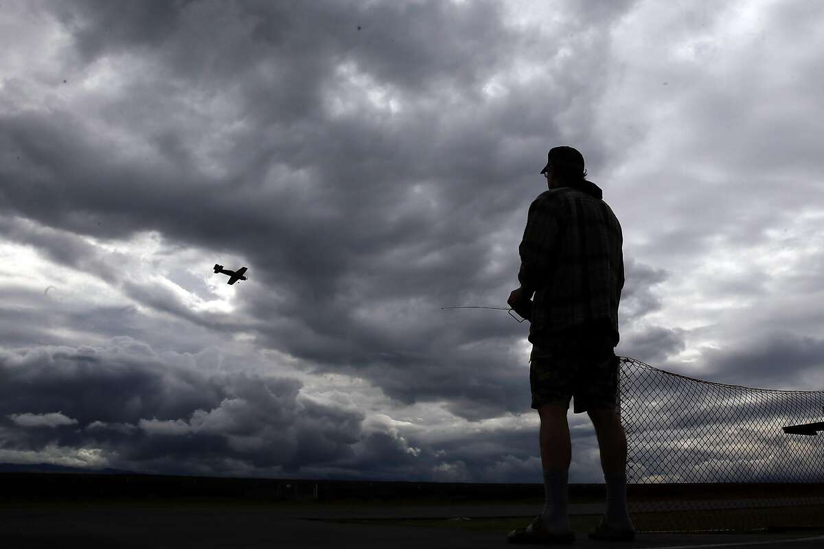 Storm clouds billow above as Kert Kerner flies his radio- controlled airplane at the Livermore Flying Electrons Club.