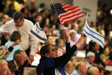A woman waves an American flag and an Israel flag during a musical presentation at the 30th annual Night to Honor Israel at Cornerstone Church in this 2011 file photo. (Jennifer Whitney/ Special to the San Antonio Express-News)
