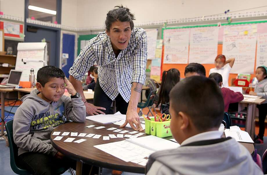 Cleveland Elementary school teacher Fernando Che (center) teaches English to third-graders Alan (left) and Christopher (right) in San Francisco. Photo: Liz Hafalia, The Chronicle