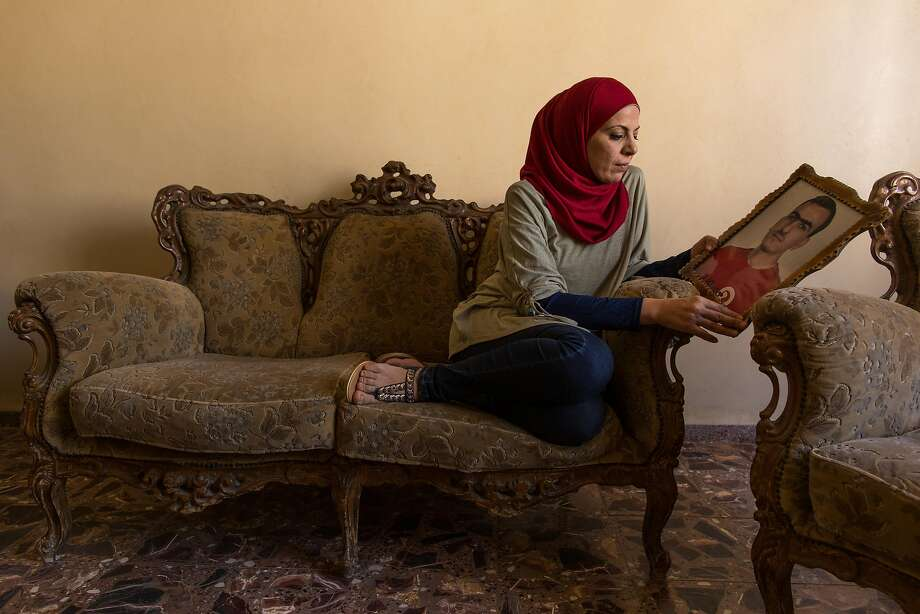 Shifa al-Qudsi holds a photo of her brother, Mahmoud Adnan al-Qudsi, who was also arrested by Israeli officials before mounting a suicide attack. Photo: RINA CASTELNUOVO, NYT