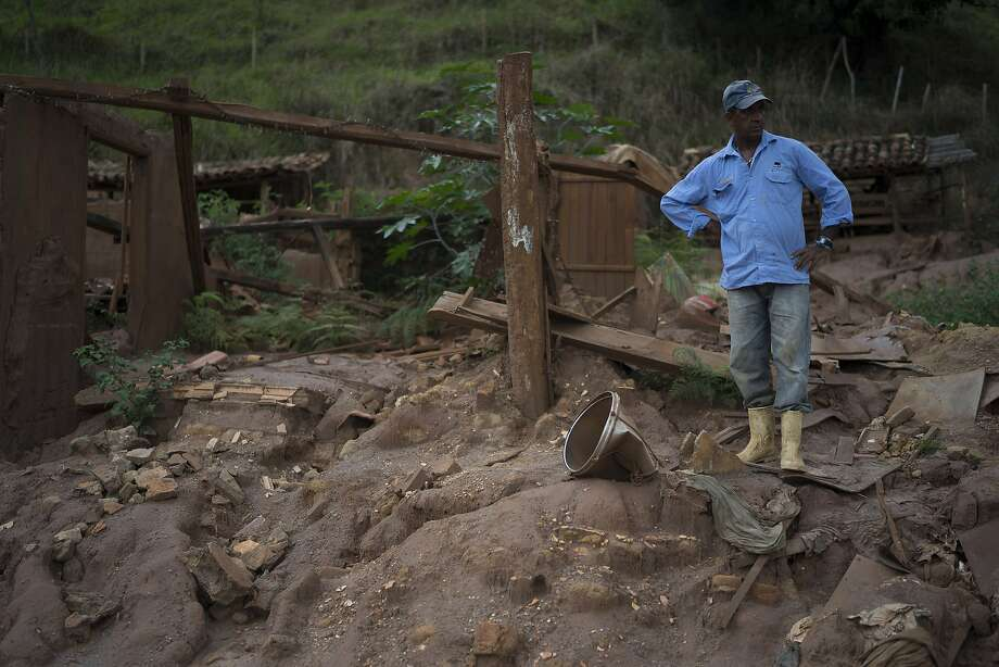 Geraldo de Oliveira stands on the rubble of his home destroyed by a 2015 mudslide unleashed by the bursting of a mine-waste basin. A tsunami of mud killed 19 people, buried entire towns and polluted hundreds of miles of rivers, streams and forest land. Some 1,200 people were made homeless. Photo: Leo Correa, Associated Press