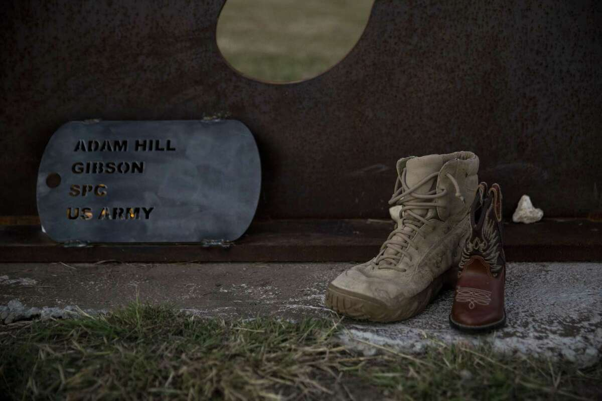 Adam Hill's favorite boots, according to his mother Annette Hill, sit in front of his memorial after the dedication ceremony for a national traveling memorial to veterans who committed suicide put together by Mission 22 at Warriors Heart Treatment Center in Bandera, Texas on October 15, 2016.