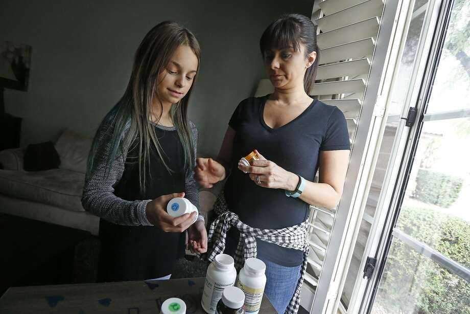 Nicole Robinson (right), with daughter Riley, 11, go over the medications Riley takes in Cave Creek, Ariz. The Robinsons are facing higher premiums for their health insurance. Photo: Ross D. Franklin, Associated Press