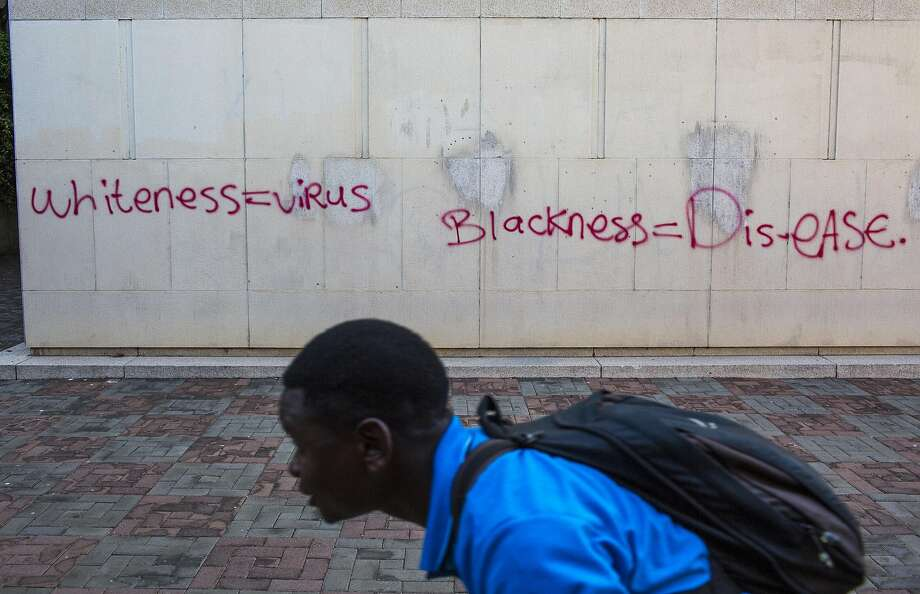 A student walks past racially charged graffiti at Wits University during recent student rallies to cut tuition in Johannesburg. Racist speech has ignited debate. Photo: JOAO SILVA, NYT