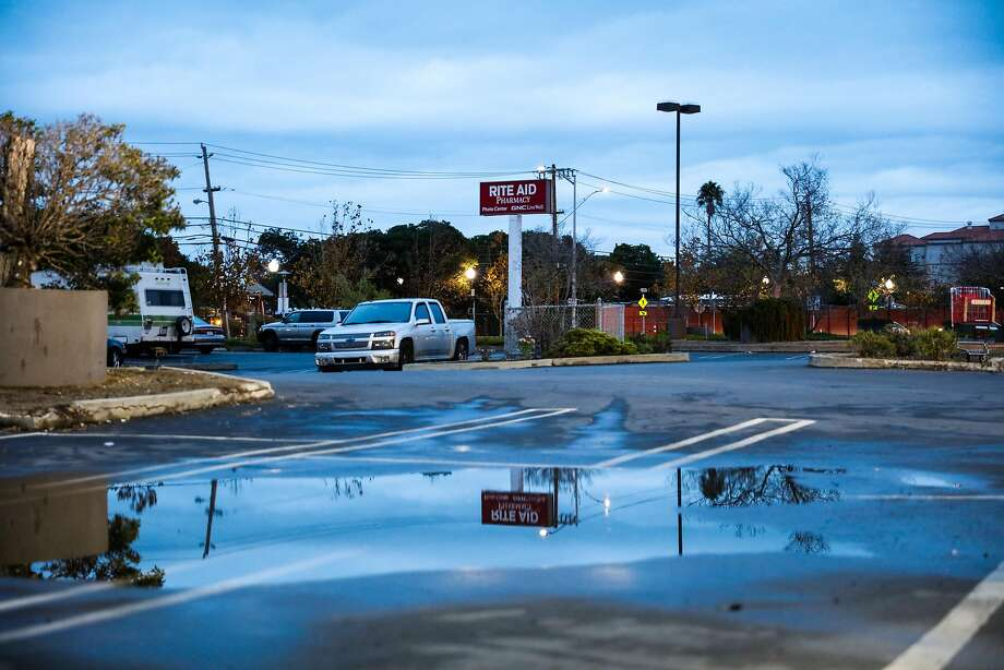 An sign for a Rite Aid pharmacy is seen reflected in the puddle of a parking lot in San Mateo. Photo: Gabrielle Lurie, The Chronicle