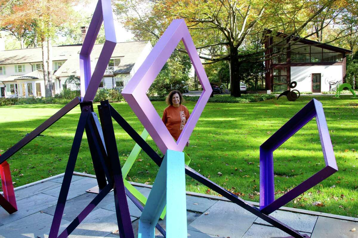Carole Eisner with one of her abstract sculptures in her yard in Weston.