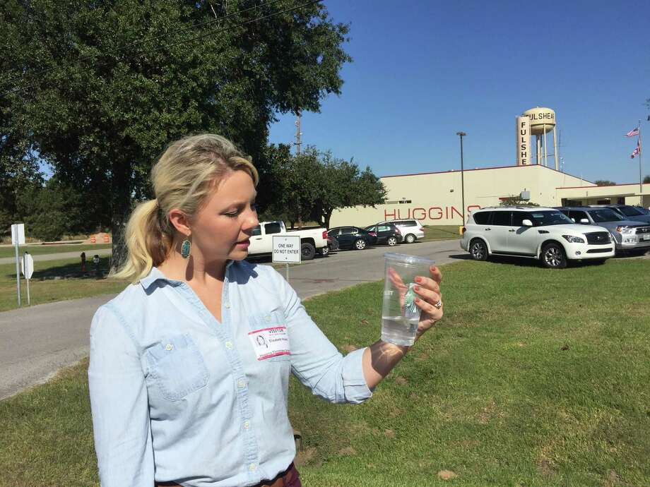 Elizabeth Hixon holds a cup she's filled from a water fountain at Huggins Elementary in Fulshear. The mother has been concerned by her daughter's remarks that it smells badly and sometimes looks yellow. Photo: Emily Foxhall