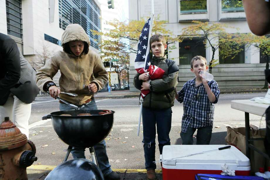 Joash Lamb, 9, holds a U.S. flag while his brothers Jacob and Jonah grill celebratory hot dogs outside the federal courthouse in Portland, Ore. on Friday. The acquittal of the armed protesters on an Oregon wildlife sanctuary has sparked mixed reactions. Photo: THOMAS PATTERSON, STR / NYTNS