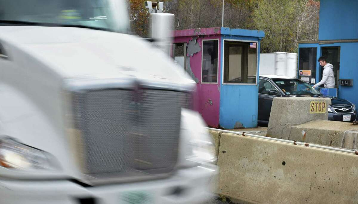 A tollbooth worker collects a toll from a motorist, right, as a truck uses a cashless lane at the Massachusetts Turnpike West Stockbridge toll plaza Friday Oct. 28, 2016 in West Stockbridge, Mass. The Massachusetts Turnpike is doing away with cash tolls and has adopted an All Electronic Tolling system. Existing toll plazas will be demolished. (John Carl D'Annibale / Times Union)