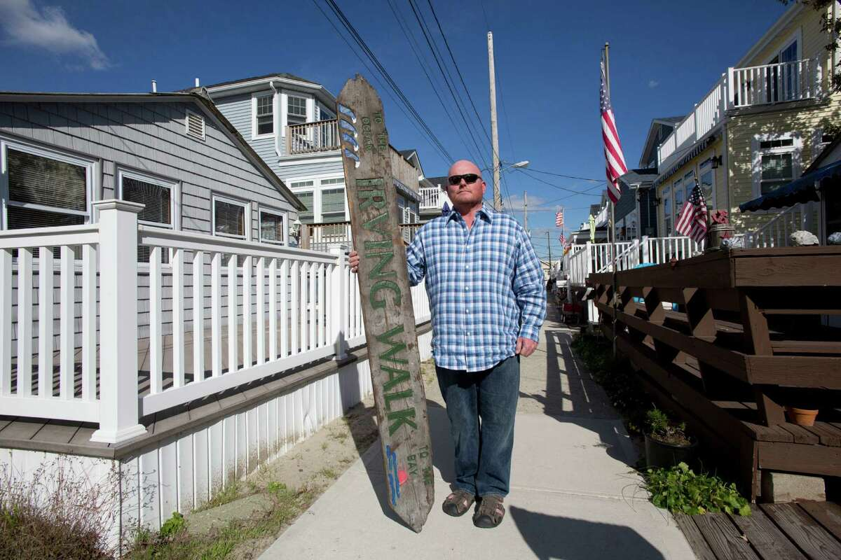 In this Oct. 26, 2016 photo, Kieran Burke poses with an Irving Walk street sign in his Breezy Point neighborhood in the Queens borough of New York. The sign had been salvaged from the debris remaining after a fire and flood swept through the neighborhood during Superstorm Sandy. A single story home, left, that survived the fire, is now surrounded by new two-story homes mounted on tall concrete foundations. Four years after the storm created a catastrophe on the coasts of New York and New Jersey, the coastline has come a long way toward recovery. But the catastrophic flooding also brought permanent changes to the shore. Some areas that have been rebuilt look dramatically different. (AP Photo/Mark Lennihan) ORG XMIT: NYML305
