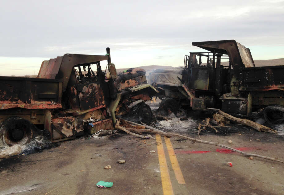 The burned hulks of heavy trucks sit on Highway 1806 near Cannon Ball, N.D., on Friday, Oct. 28, near the spot where protesters of the Dakota Access pipeline were evicted from private property a day earlier. Authorities say protesters burned several pieces of construction equipment Thursday during a chaotic confrontation with law enforcement. (AP Photo/James MacPherson) Photo: James MacPherson, STF / Copyright 2016 The Associated Press. All rights reserved.