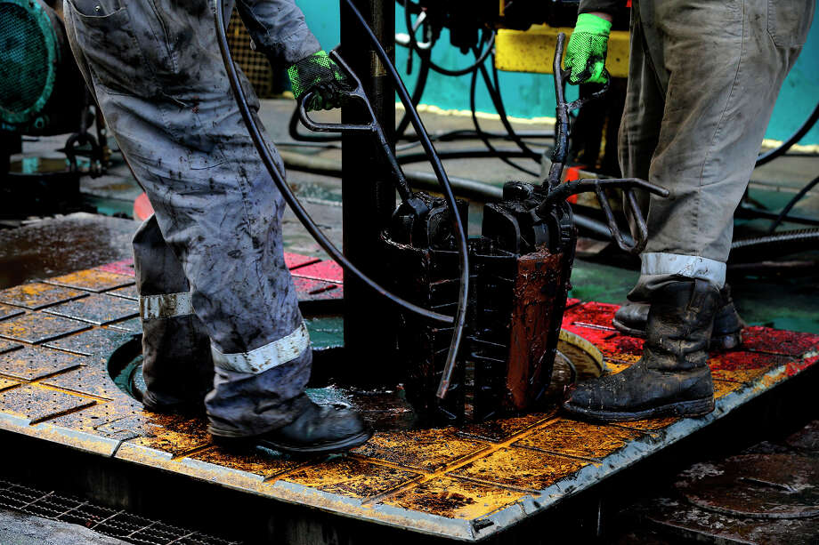 Floor hands work at a well in South Texas this summer. Active rigs in the Eagle Ford Shale peaked at 210 in 2014 and have since slid to less than 40. ConocoPhillips says it is adding two rigs there. Photo: John Davenport, Staff / ©San Antonio Express-News/John Davenport