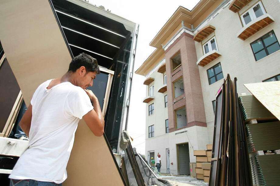 Luis Artate carries cabinets into the Camden Travis complex during its construction in 2009. Camden Property Trust says it expects 23,000 new apartment units to open in Houston in 2016. Photo: Mayra Beltran, Staff / Houston Chronicle