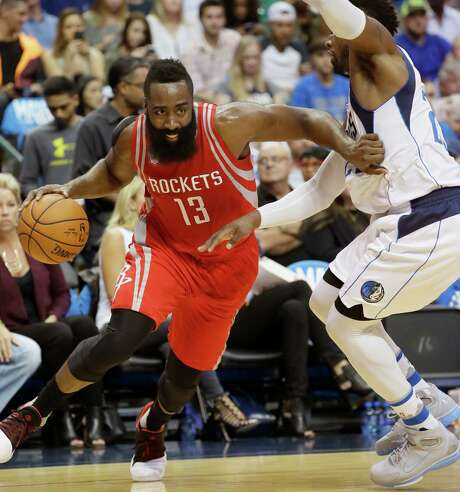 Rockets guard James Harden, left, finds the Mavs' Wesley Matthews to be only a temporary obstacle. Photo: LM Otero, STF / AP