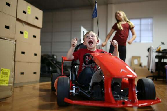 Connor Ellerhorst, 5, shows his excitement for getting to sit inside an Arrow Smart Kart as his sister Kaylee, 10, dances in the back at the Actev Motors headquarters in Mountain view as her brother Connor, 5, waits on the sidelines on Thursday, Oct 27, 2016.