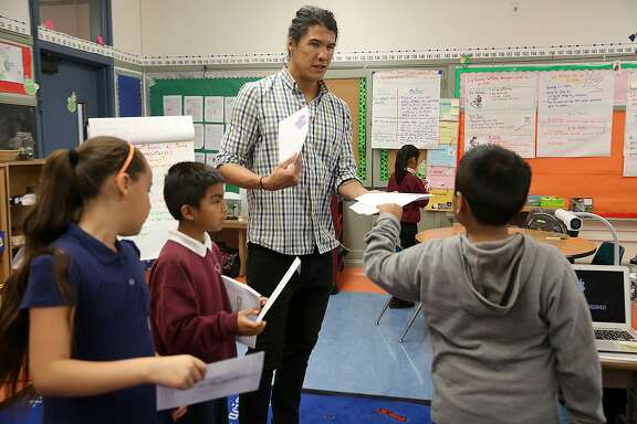 Cleveland Elelmentary school teacher Fernando Che hands word envelopes to his third graders including on Thursday, October 27, 2016, in San Francisco, Calif.