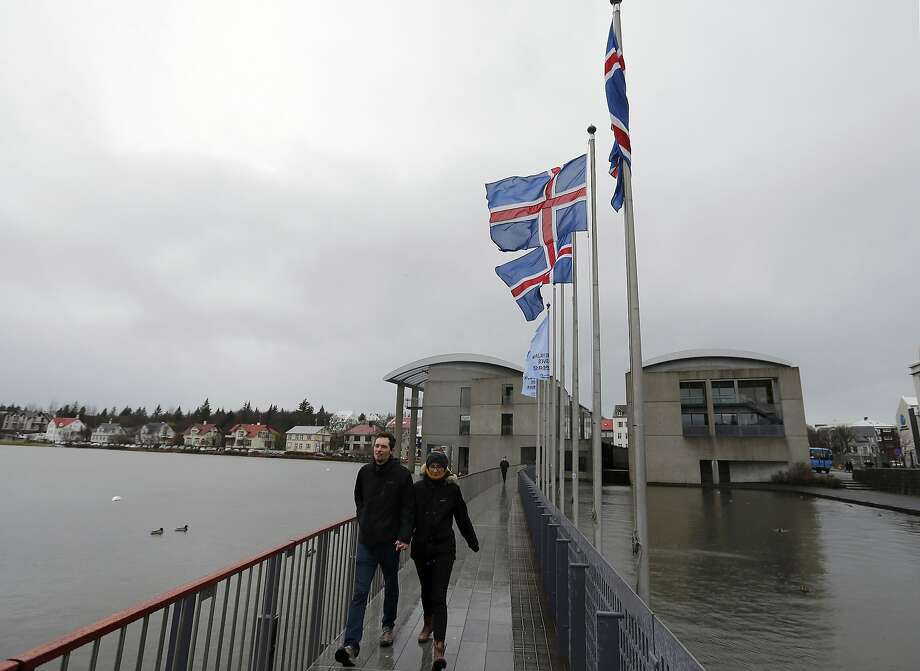 A couple exit the town hall polling station after voting in Reykjavik, Iceland. The ruling Independence Party took the early lead over challengers in parliamentary elections. Photo: Frank Augstein, Associated Press