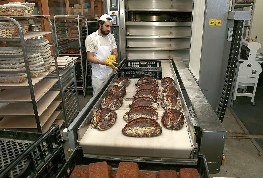 Bread comes from the oven at Tartine Manufactory. Photo: Liz Hafalia / The Chronicle