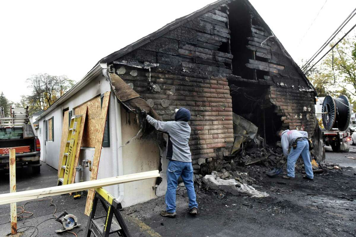 Brothers Andrew Klouse, left, and Anthony Klouse, who are friends with the tavern owner, clean up fire debris on Saturday, Oct. 29, 2016, at Blessings Tavern in Colonie, N.Y. (Cindy Schultz / Times Union)