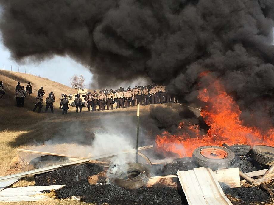 FILE--In this Oct. 27, 2016, file photo, tires burn as armed soldiers and law enforcement officers stand in formation to force Dakota Access pipeline protesters off private land in Morton County, N.D., where they had camped to block construction. On the same day seven defendants celebrated acquittal in Portland, Ore., for their armed takeover of a federal wildlife refuge in Oregon, nearly 150 protesters camped out in North Dakota to protest an oil pipeline were arrested. (Mike McCleary/The Bismarck Tribune via AP, file) Photo: Mike McCleary, Associated Press