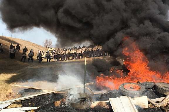 FILE--In this Oct. 27, 2016, file photo, tires burn as armed soldiers and law enforcement officers stand in formation to force Dakota Access pipeline protesters off private land in Morton County, N.D., where they had camped to block construction. On the same day seven defendants celebrated acquittal in Portland, Ore., for their armed takeover of a federal wildlife refuge in Oregon, nearly 150 protesters camped out in North Dakota to protest an oil pipeline were arrested. (Mike McCleary/The Bismarck Tribune via AP, file)
