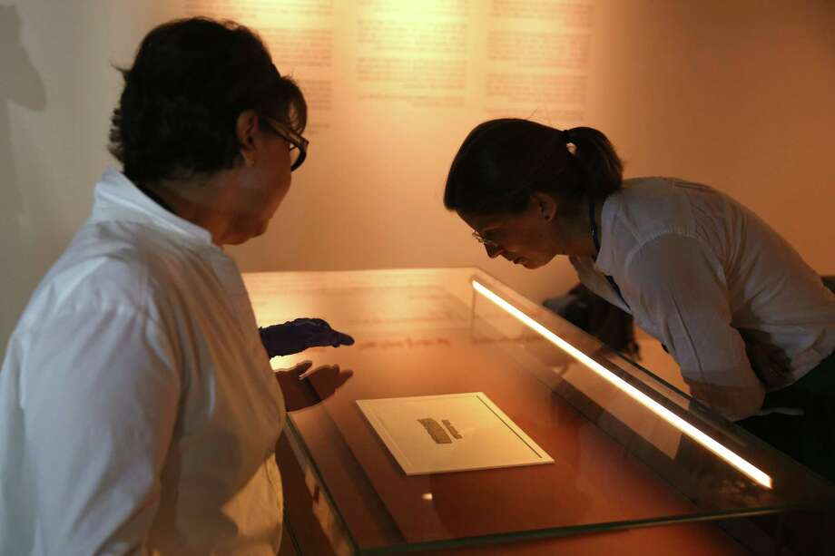 A woman looks at an ancient papyrus manuscript dating back to the time of the First Temple (seventh century BCE) during a press call in Jerusalem on October 26, 2016.  The rare find was exposed in an enforcement operation initiated by the Israel Antiquities Authority Unit for the Prevention of Antiquities Robbery. The document written on papyrus bears the name of the city of Jerusalem and is the earliest extra-biblical source to mention Jerusalem in Hebrew writing. / AFP PHOTO / MENAHEM KAHANAMENAHEM KAHANA/AFP/Getty Images Photo: MENAHEM KAHANA, Staff / AFP or licensors