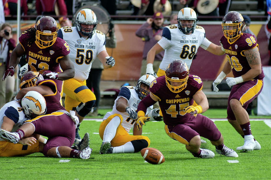 Central Michigan University's Joe Ostman, center, jumps on a loose ball fumbled by Kent State's Justin Rankin during the first quarter on Saturday at Kelly/Shorts Stadium in Mt. Pleasant. Kent State won 27-24. Photo: NICK KING | Nking@mdn.net