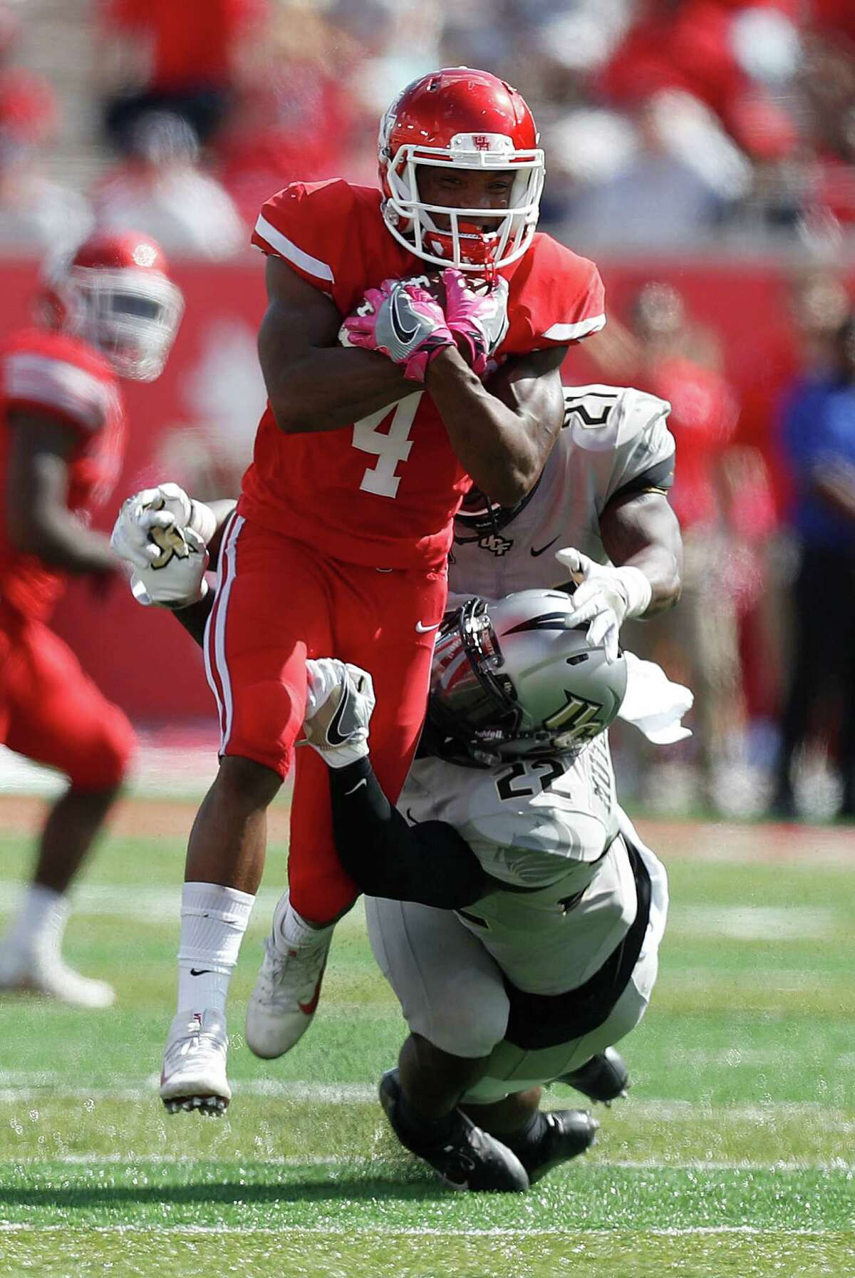 Houston Cougars D'Eriq King (4) gains yardage as UCF Knights defensive backs Drico Johnson (21) and T.J. Mutcherson (22) try to bring him down during the fourth quarter of a college football game at TDECU Stadium, Saturday,Oct. 29, 2016 in Houston.