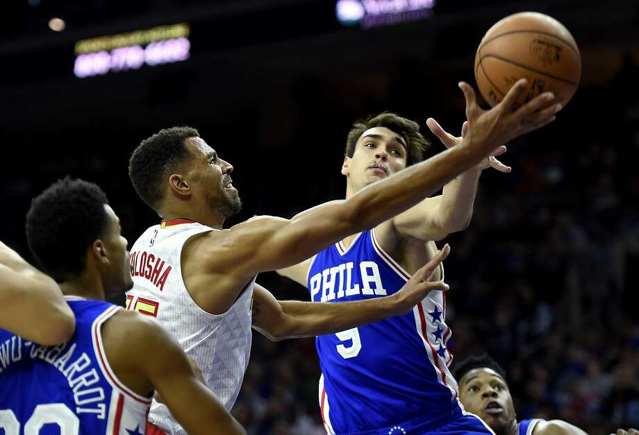 Atlanta's Thabo Sefolosha drives to the basket past Philadelphia's Dario Saric. Photo: Michael Perez, Associated Press
