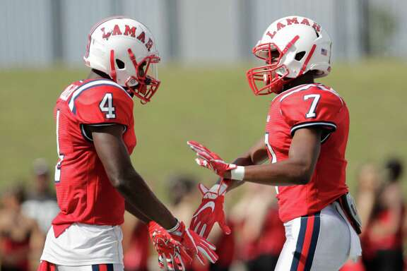 Lamar Texans wide receiver Al'vonte Woodard (4) and Lamar Texans wide receiver Ty Holden (7) celebrate after a touchdown during the high school football game between the Lamar Texans and the Bellaire Cardinals at Delmar Stadium in Houston, TX on Saturday, October 29, 2016.  The Texans lead the Cardinals 41-10 at halftime.