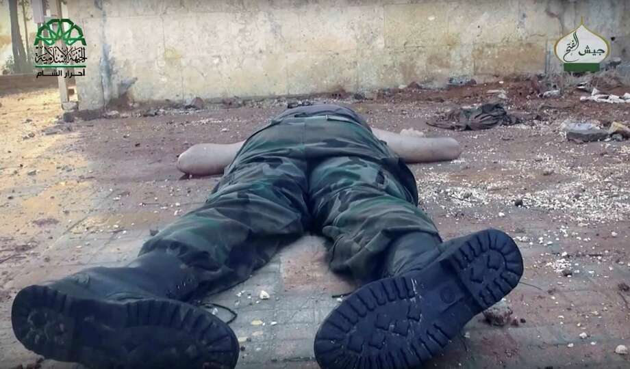 This still image taken from undated drone footage, posted online by the communications arm of Ahrar al-Sham militant group, purports to show a dead Syrian soldier, in an Assad neighborhood of Aleppo, Syria. Syrian government forces launched a counteroffensive Saturday, Oct. 29, 2016, under the cover of airstrikes in an attempt to regain control of areas they had lost to insurgents the day before in the northern city of Aleppo, activists and state media said. (Ahrar al-Sham, militant video, via AP) Photo: Uncredited, UGC / Ahrar al-Sham