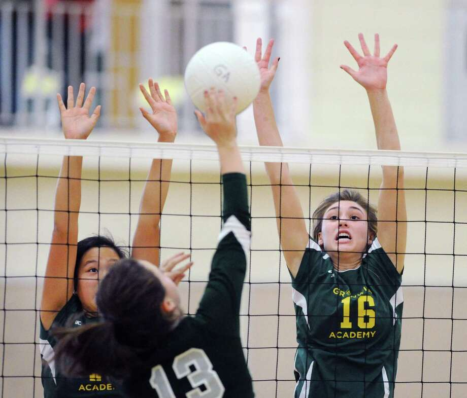 At right, Madlin Decker (#16), right, of GA and teammate Grace Zhao, left, attempt to block the spike of Berkshire School's Abbey Turner (#13) during the high school volleyball match between Greenwich Academy and Berkshire School at Greenwich Academy, Conn., Oct. 29, 2016. Photo: Bob Luckey Jr. / Hearst Connecticut Media / Greenwich Time