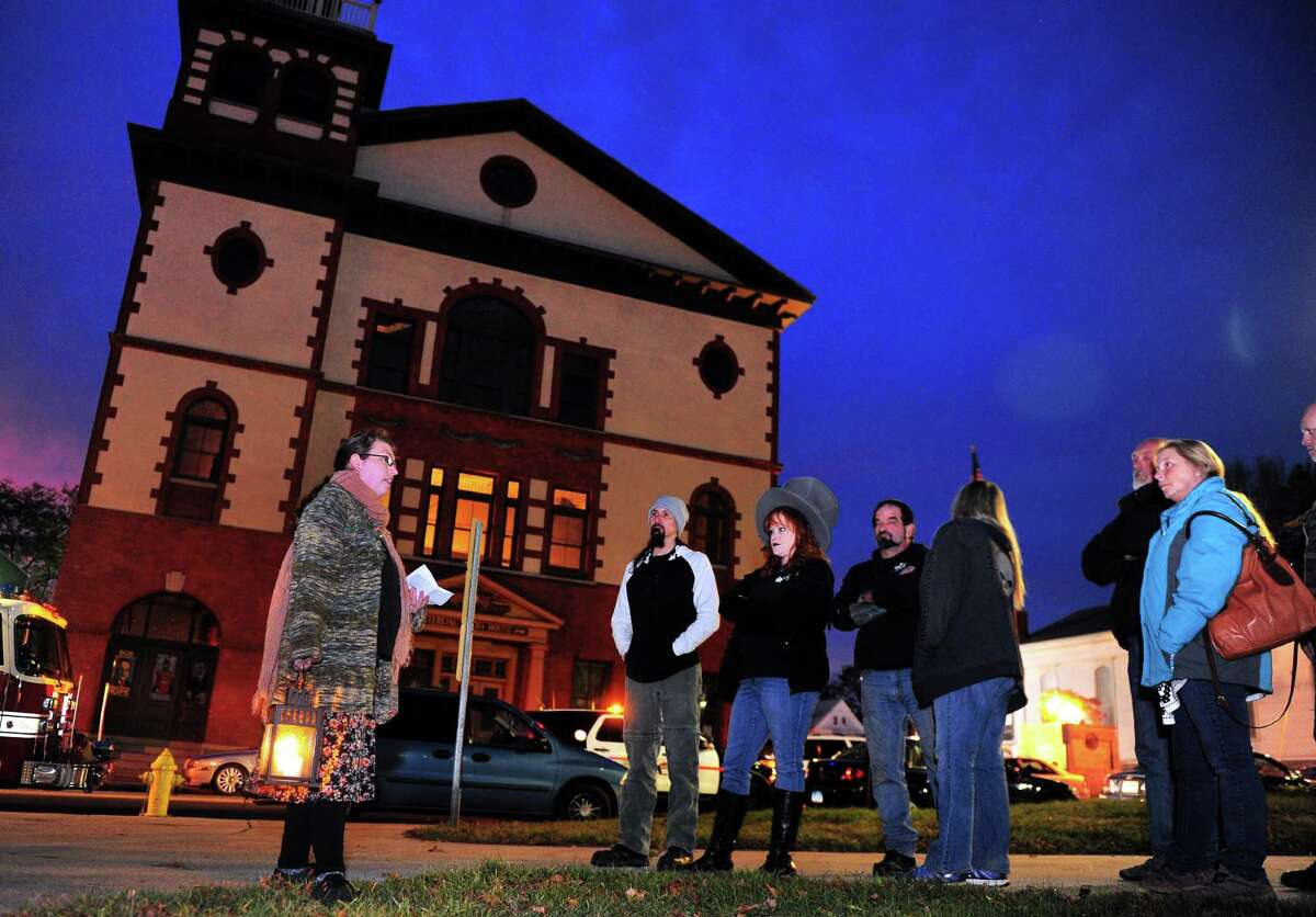 Tour guide Jaimee Mansfield, of Seymour, left, leads a group through the Haunted Lantern Tour starting on the historic Derby Green along Elizabeth Street in downtown Derby, Conn., on Saturday Oct. 29, 2016. People gathered for the tour which stopped at 11 historic and allegedly haunted spots around Derby withing walking distance of the green. In the background is the historic Sterling Opera House and money raised through the tour is going to its restoration.