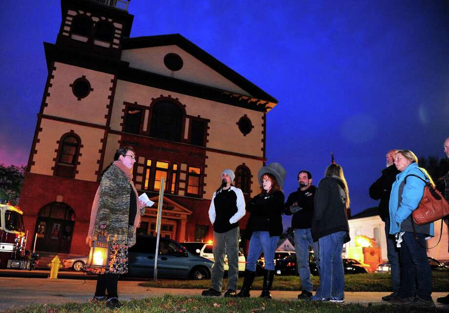Tour guide Jaimee Mansfield, of Seymour, left, leads a group through the Haunted Lantern Tour starting on the historic Derby Green along Elizabeth Street in downtown Derby, Conn., on Saturday Oct. 29, 2016. People gathered for the tour which stopped at 11 historic and allegedly haunted spots around Derby withing walking distance of the green. In the background is the historic Sterling Opera House and money raised through the tour is going to its restoration. Photo: Christian Abraham, Hearst Connecticut Media / Connecticut Post