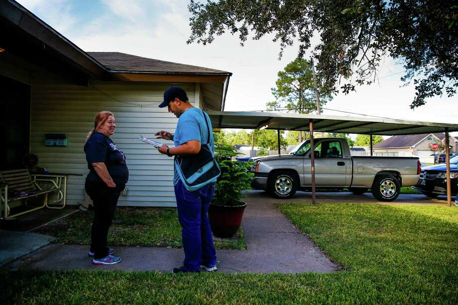 Texas Organizing Project's John Rodriguez talks to Nancy Welcome as he works to get minority voters in Harris County to commit to vote. Photo: Michael Ciaglo, Staff / © 2016  Houston Chronicle