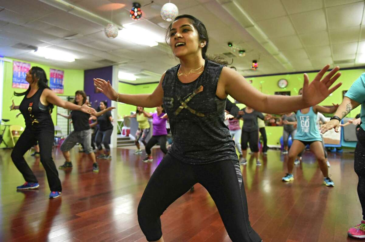 Fitness instructors Angana Patel, left, and Payal Patel, center, lead a BollyX fitness class at Move Fitness on Wednesday, Sept. 21, 2016 in Albany, N.Y. BollyX is a Bollywood-inspired dance fitness program. (Lori Van Buren / Times Union)