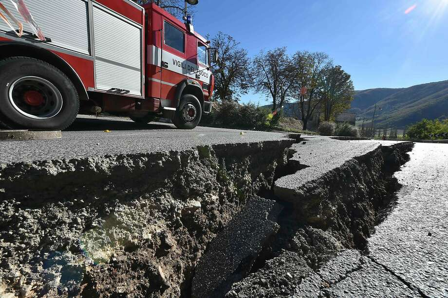 A vehicle of the firefighters passes near cracks on the road outside the center of Norcia after a 6.6 magnitude earthquake on October 30, 2016. It came four days after quakes of 5.5 and 6.1 magnitude hit the same area and nine weeks after nearly 300 people died in an August 24 quake that devastated the tourist town of Amatrice at the peak of the holiday season. Italy's most powerful earthquake in 36 years dealt a new blow Sunday to the country's seismically vulnerable heart, sending terrified residents fleeing for the third time in nine weeks and flattening a revered six-century-old church. / AFP PHOTO / ALBERTO PIZZOLIALBERTO PIZZOLI/AFP/Getty Images Photo: ALBERTO PIZZOLI, AFP/Getty Images