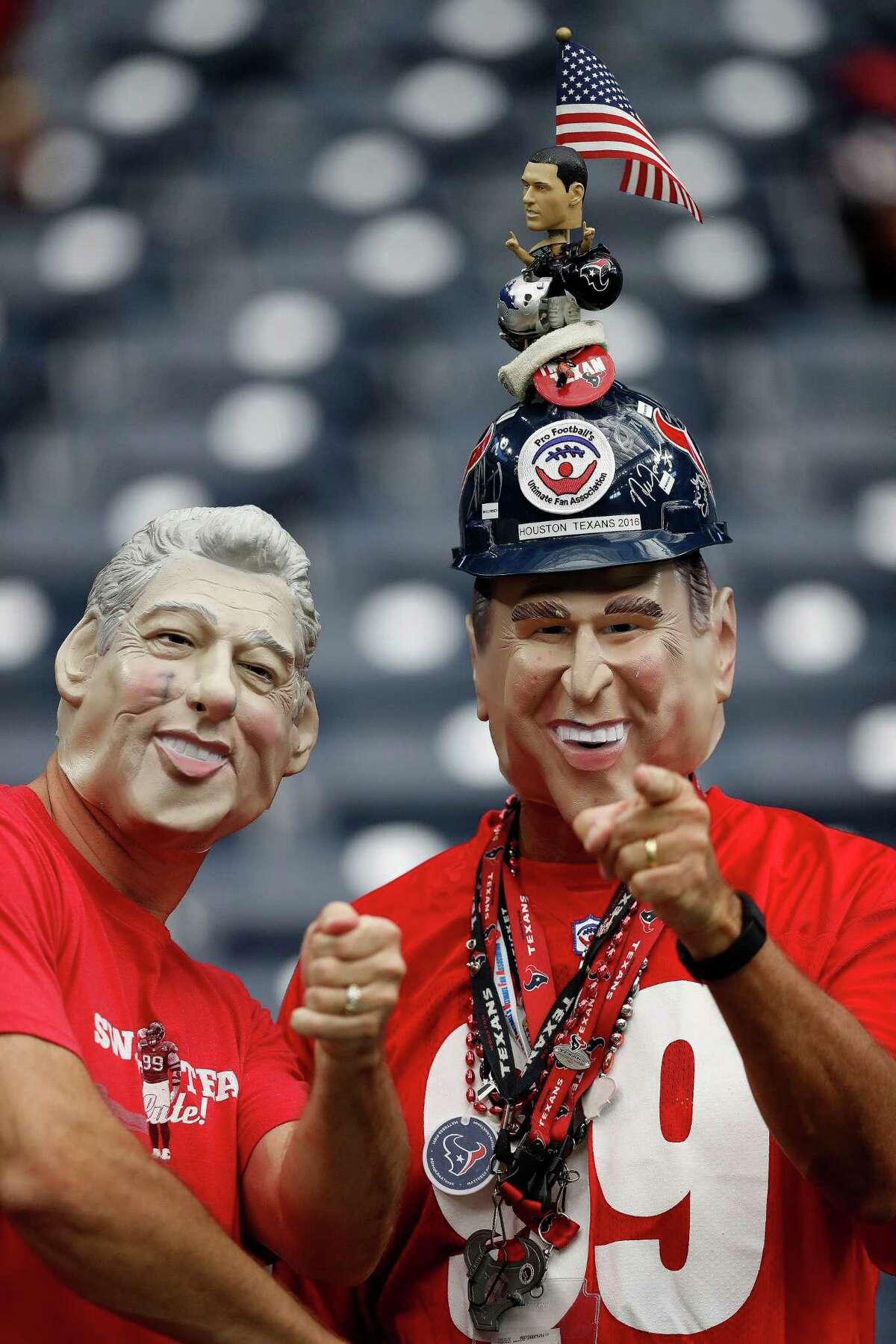 Houston Texans fan Mark Baughman wearing a George Bush mask hams it up with