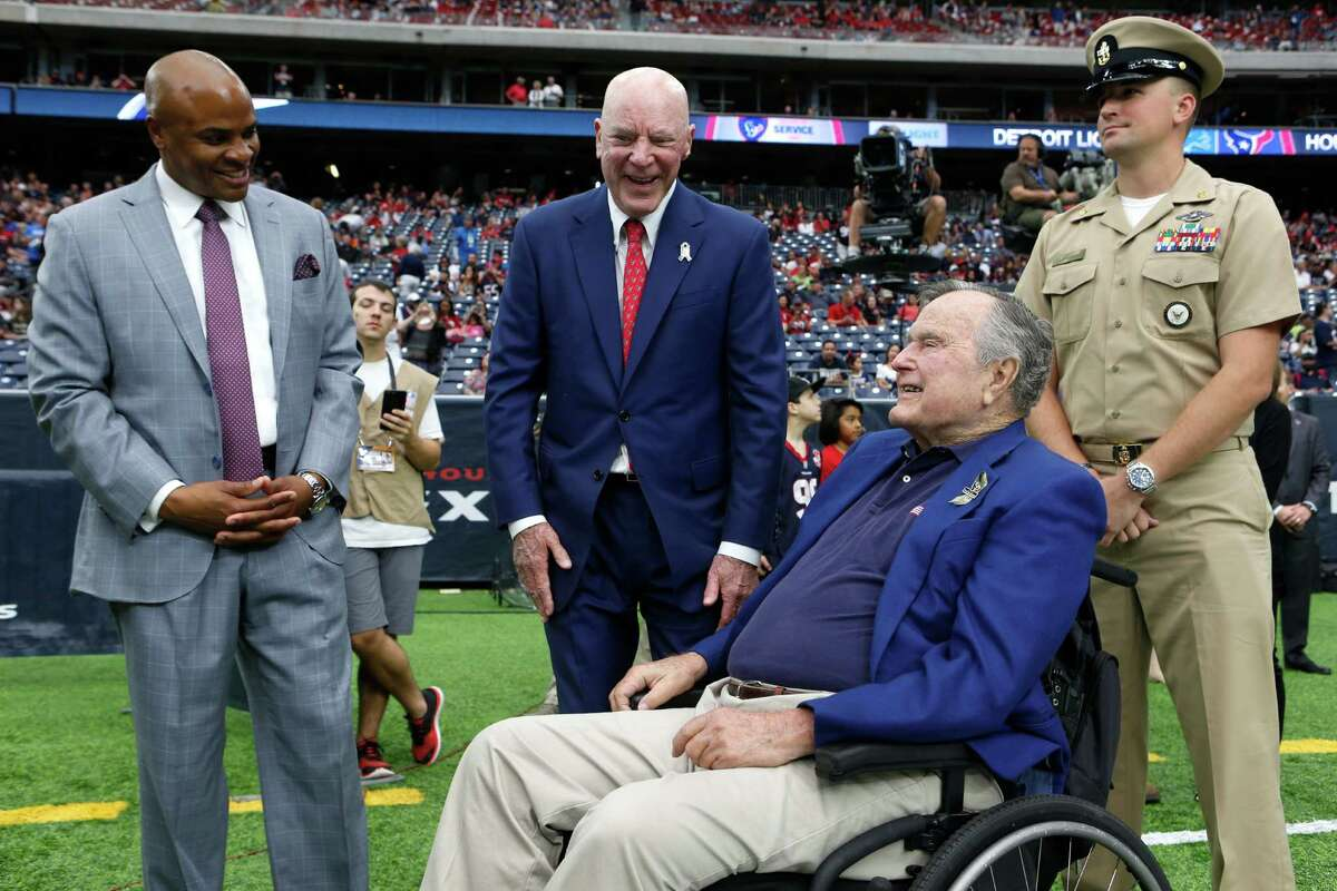 Houston Texans general manager Rick Smith and owner Bob McNair stans with former President George H.W. Bush before an NFL football game against the Detroit Lions at NRG Stadium on Sunday, Oct. 30, 2016, in Houston.