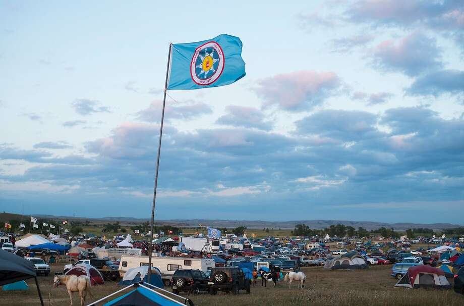 A Standing Rock Sioux flag flies over a protest encampment near Cannon Ball, North Dakota where members of the Standing Rock Sioux tribe and their supporters have gathered to voice their opposition to the Dakota Access oil Pipeline (DAPL), September 3, 2016. Drive on a state highway along the Missouri River, amid the rolling hills and wide prairies of North Dakota, and you'll come across a makeshift camp of Native Americans -- united by a common cause. Members of some 200 tribes have gathered here, many raising tribal flags that flap in the unforgiving wind. Some have been here since April, their numbers fluctuating between hundreds and thousands, in an unprecedented show of joint resistance to the nearly 1,200 mile-long Dakota Access oil pipeline. / AFP PHOTO / Robyn BECKROBYN BECK/AFP/Getty Images Photo: ROBYN BECK, AFP/Getty Images