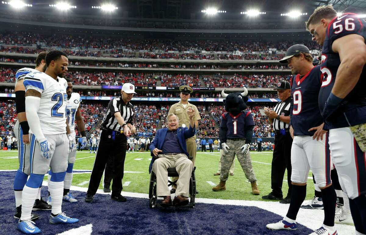 Former President George H.W. Bush flips the coin before an NFL football game between the Houston Texans and Detroit Lions at NRG Stadium on Sunday, Oct. 30, 2016, in Houston.