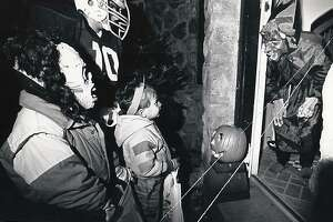Dressed as a monster, Mark Strom, of Stamford, greets children trick-or-treating on Oct 31,1988. The Strom family dressed up and decorated their castle-like home on Oakdale Road for Halloween for many years.
