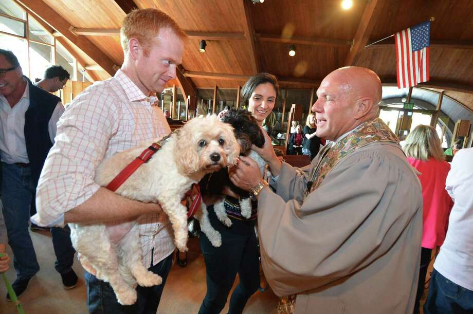 Robert Lounihan and wife Maura Bonanni with their Cavacho's Lacey and Max as Pastor John Livinstion blesses the animals during a special Sunday service at the United Church of Rowayton on Sunday October 30, 2016 in Norwalk Conn. Photo: Alex Von Kleydorff / Hearst Connecticut Media / Connecticut Post