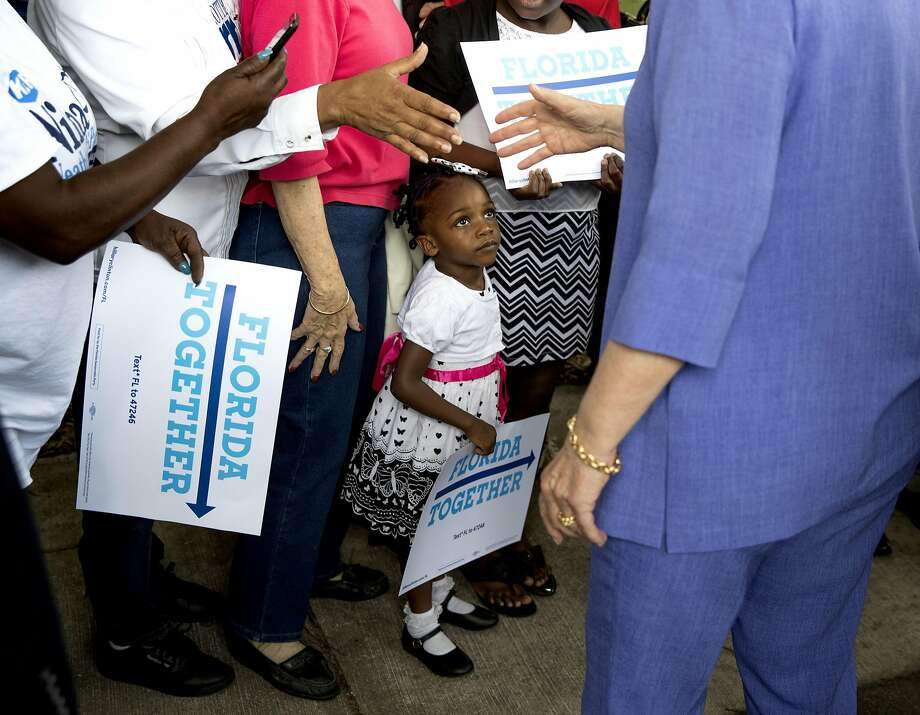 A girl watches as Hillary Clinton makes a surprise stop at an early voting office in Pompano Beach, Fla. Photo: DOUG MILLS, NYT